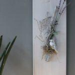 WD109 - Frühlingshafte Wanddeko! Holzbrett weiß gebeizt, dekoriert mit natürlichen Materialien, einem silberfarbenen Vogel und künstlichen Lavendel! Preis 39,90€ Größe 20x60cm