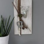 HE69 - Holzbrett weiß gebeizt, dekoriert mit natürlichen Materialien, Filzbändern, einem Hirschkopf, einer künstlichen Sukkulente und einem Miniglockenherz! Preis 64,90€ Größe 30x60cm
