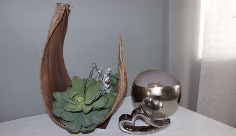 TD251-Ansicht Vorne - Großes Kokosblatt als Tischdeko, von beiden Seiten dekoriert mit einer großen und kleine künstlichen Sukkulente, natürlichen Materialien, künstlichen Efeu und einer großen Edelstahlkugel! Preis 74,90€ Breite ca. 25cm Höhe ca. 40cm Größen können zum Original abweichend sein! Keramikherz Preis 7,90€ Breite 16cm Metallwindlicht innen glasiert Preis 29,90€ Größe 18x16,5 cm
