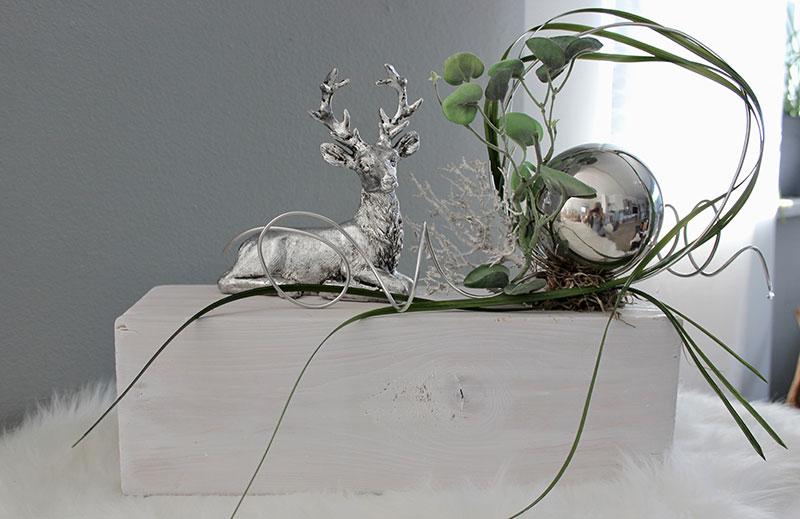 HE118 - Holzblock als Tisch, Sideboard oder Fensterdeko! Holzblock weiß gebeizt, dekoriert mit natürlichen Materialien, künstlicher Efeuranke, künstlichen Gräsern, Aludraht, silberfarbigen Hirschen und einer Edelstahlkugel! Preis 69,90€ Breite ca 50cm